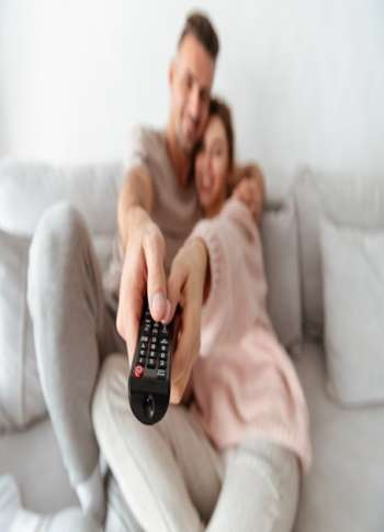 Smiling loving couple sitting on couch together and watching TV. Focus on TV remote
